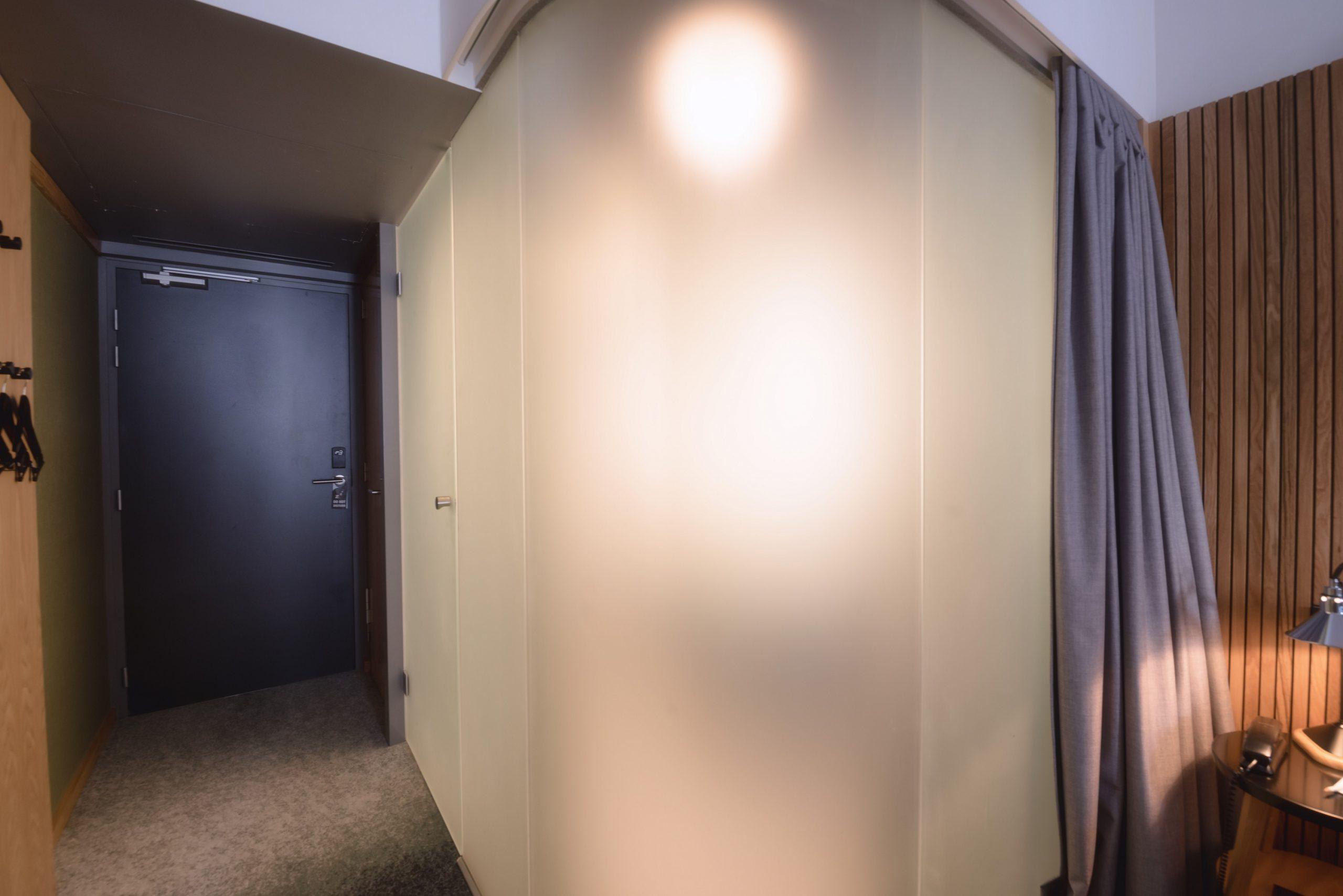 Satiniertes Glas, das in einem Hotelzimmer das Bad vom Schlafbereich trennt