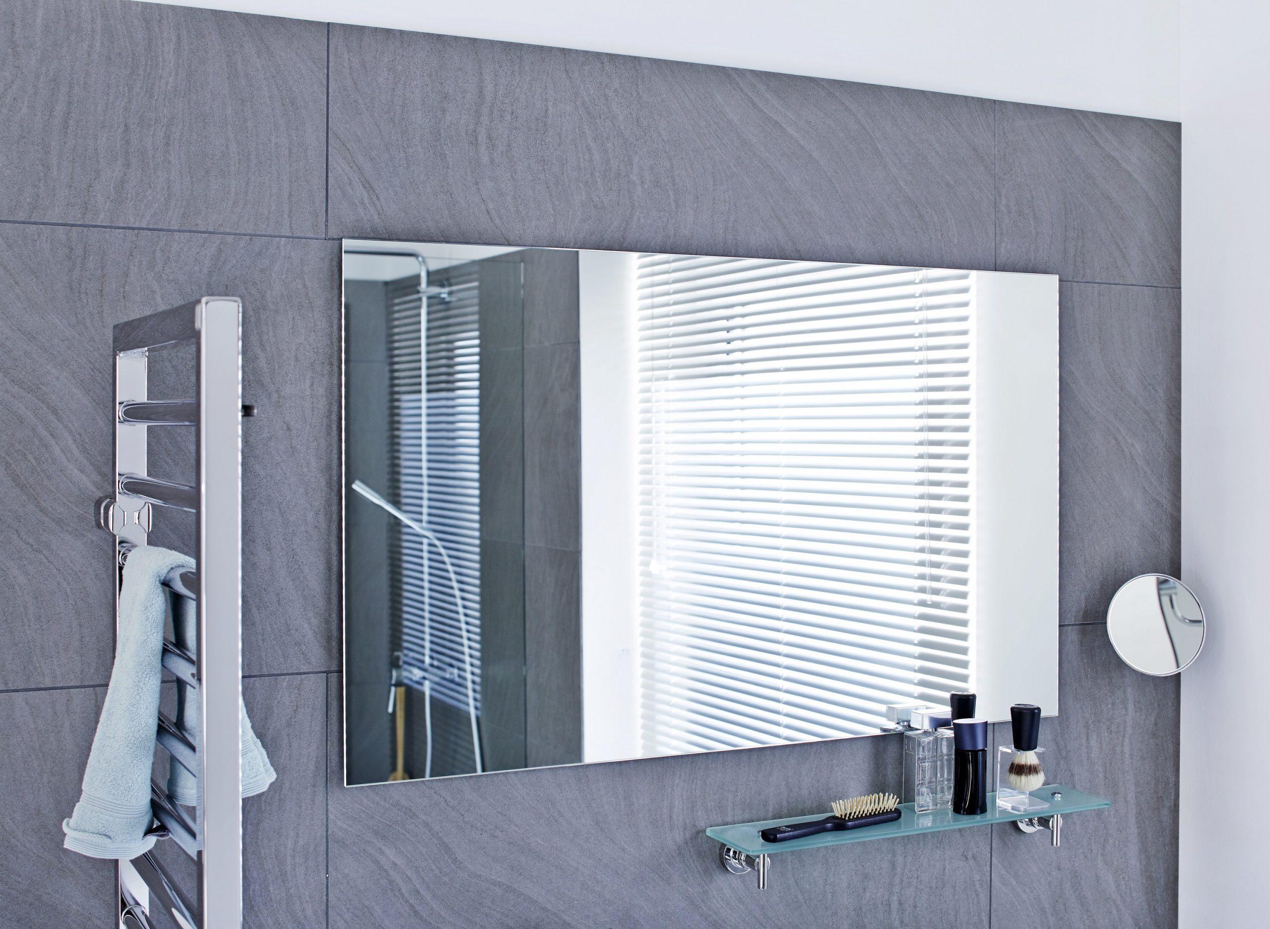 Wandspiegel im Bad vor grauen Fliesen